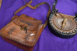 Two vintage leather bags having stitched and embossed details.