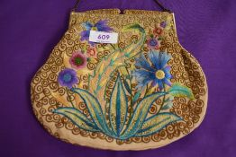 An antique clasp framed evening bag having unusual filigree clasp and colourful floral embroidery to
