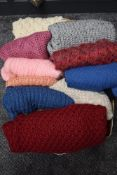 A box full of hand knitted jumpers and cardigans.