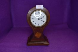 An Edwardian mahogany mantel clock having inlaid detail to waisted front and roman numerals to