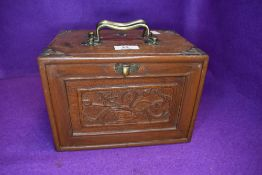 A vintage miniature oak chest of drawers containing a selection of games having inlaid and carved