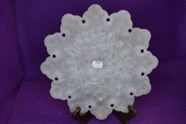 An intricately carved semi opaque plate,mineral or similar, having grape vine detail.