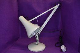 A white anglepoise desk light.