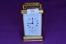 A Thwaites and reed carriage clock having bevelled glass gallery and to sides.