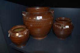Three vintage stoneware urns/planters of varying size.