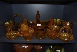 A collection of amber glass items amongst which are goblets, bowls, decorative items and more.