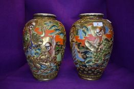 A pair of hand painted Japanese vases having relief moulded pattern possibly depicting the eight