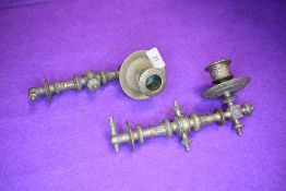 A pair of ornately decorated antique detachable piano or carriage candle sticks