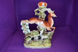 A Staffordshire flat back spill vase depicting leaping dog and deer.