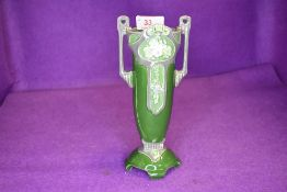 An Eichwald twin handled vase having strong art nouveau styling with green ground and grey accents