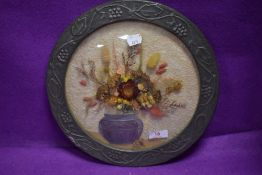 An arts and crafts style embossed metal framed dried flower display having convex glass front.
