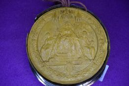 An unusual large antique wax seal or similar.