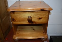 A modern pine bedside table with drawer