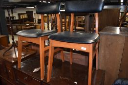 A pair of vintage dining chairs having stained frames and vinyl seats and backs