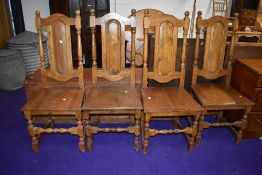 A set of four traditional oak colonial style dining chairs having panel backs and solid seats