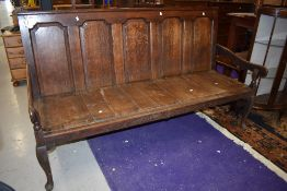 An 18th Century oak settle having five panelled back , shaped arms and cabriole legs, width