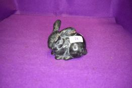 A cast metal baby rabbit having marble effect.