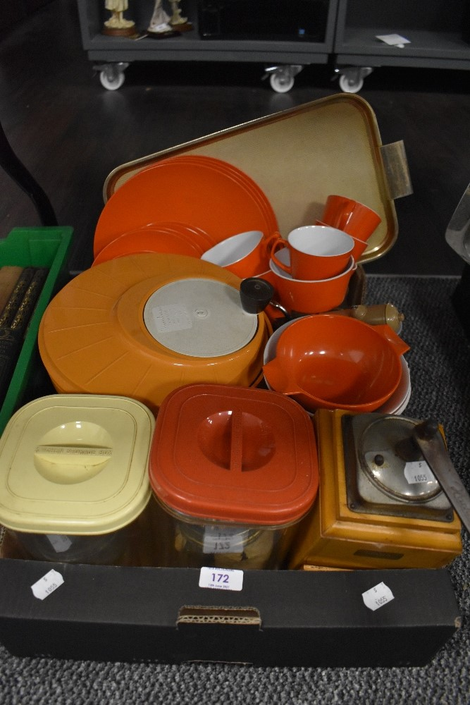 A collection of retro tupperware including orange Melaware plates and cups.