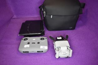 A DJI drone camera with bag and accessories.