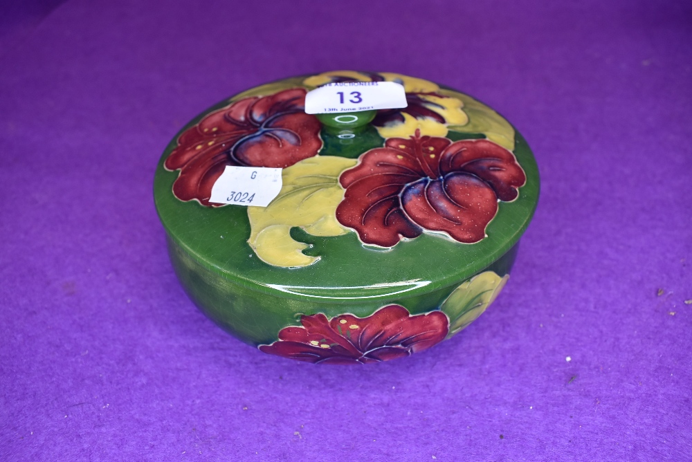 A vintage Moorcroft lidded bowl having green and blue ground and red and yellow hibiscus pattern.