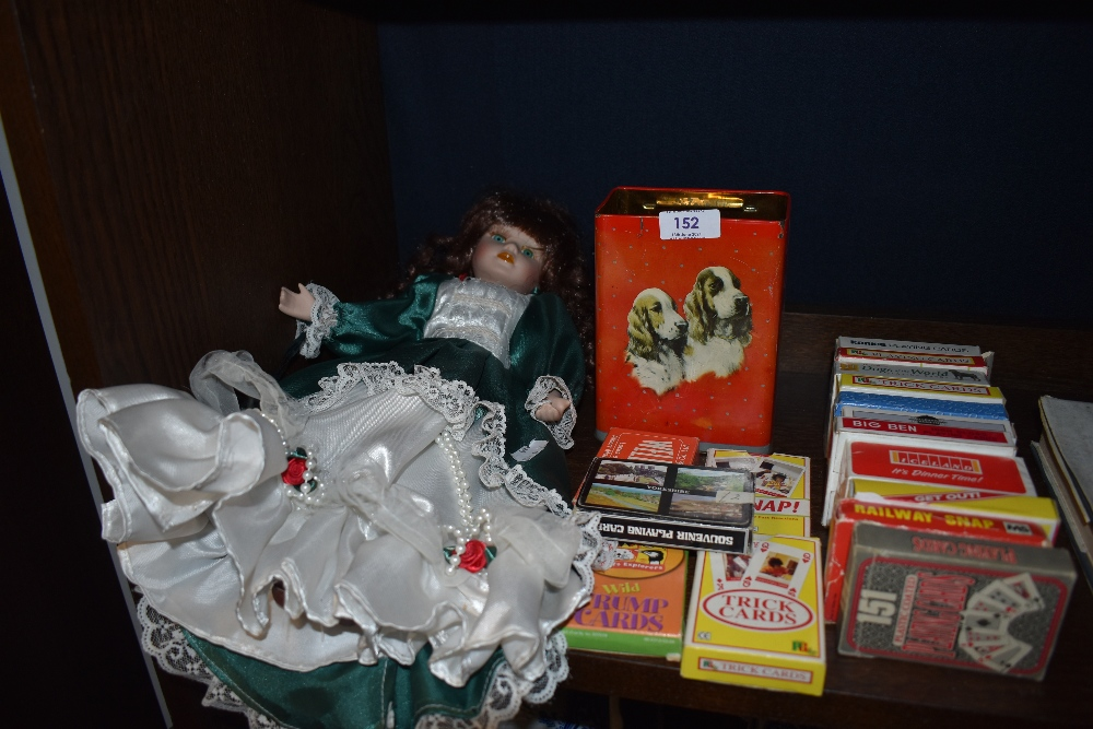 A good quantity of packs of playing cards a vintage tin and a doll.