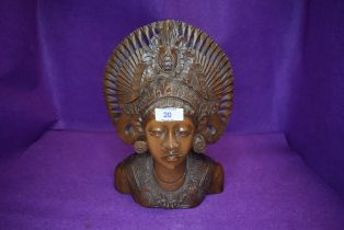 An intricately carved ethnic styled wooden bust.
