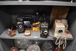An assortment of cameras,binoculars,Cine Kodak and an Aldis projector.