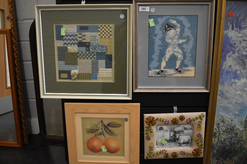 A selection of prints and needle work including wool sampler