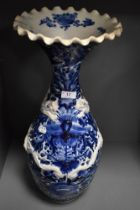 A large standing blue and white wear Chinese vase having raised dragon motif and scalloped rim