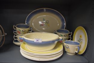 A collection of Susie cooper plates,soup mugs and platters having cream ground with blue border