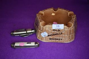 A vintage Old Bushmills Whiskey ashtray and two pen knives/multi tools,one having spoon and fork.
