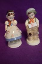 A pair of Royal Dux figures of a Shcool boy and girl