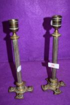 A pair of antique brass cast candle sticks having column stems of crucifix bases