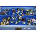 A jewellery box containing a large selection of costume jewellery rings of various designs