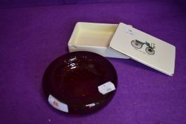 A ruby red control bubble glass dish and ceramic lidded container with transport imagery