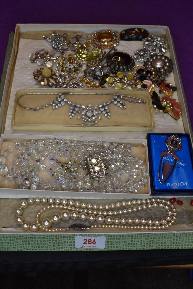 A vintage chocolate box containing a selection of costume brooches and necklaces including crystal