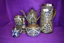 A selection of Doulton Lambeth table wares havine HM silver rims and fitments including water jug