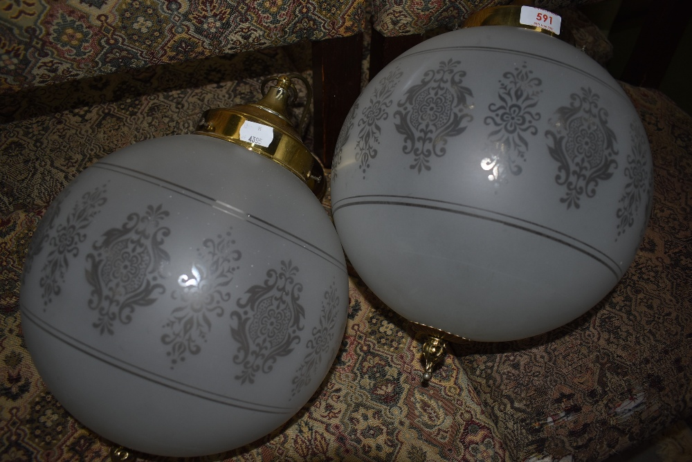 A pair of etched glass globe light fittings having brass gallery