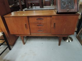 A vintage sideboard, compact size with central three drawer section flanked by cupboards, tapered