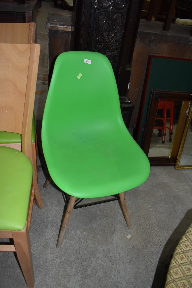 A modern plastic moulded chair having beech wood legs on atomic frame