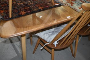 A light Ercol extending dining table having double centre leaf (Grand Windsor) and a set of six (