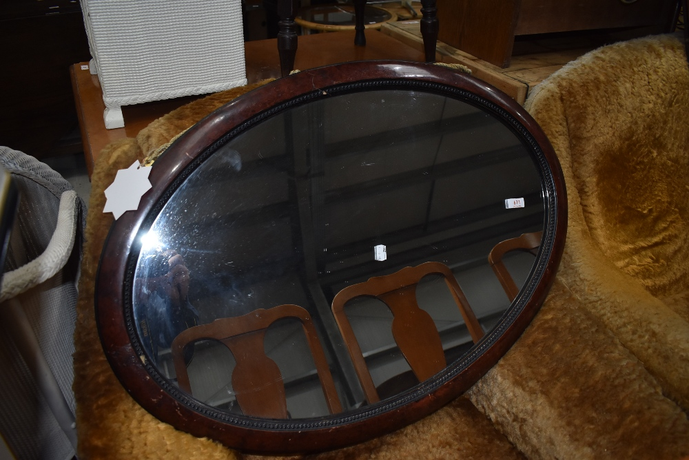 An over mantle mirror having oval scumbal finished frame