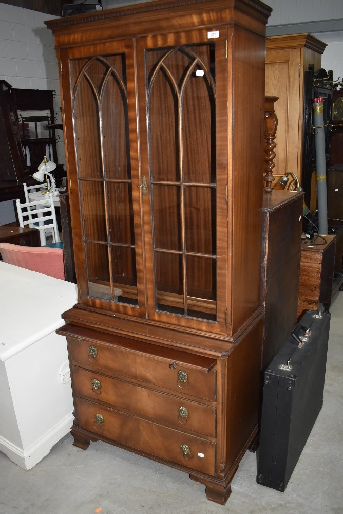 A reproduction Regency style bookcase/drinks cabinet having drawer base, lion mask handles and slide