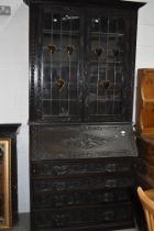 A 19th Century dark oak Jacobean style bureau bookcase, black forest and arts and crafts influences