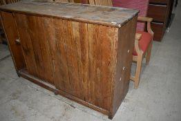 A rustic pine side cabinet having sliding doors