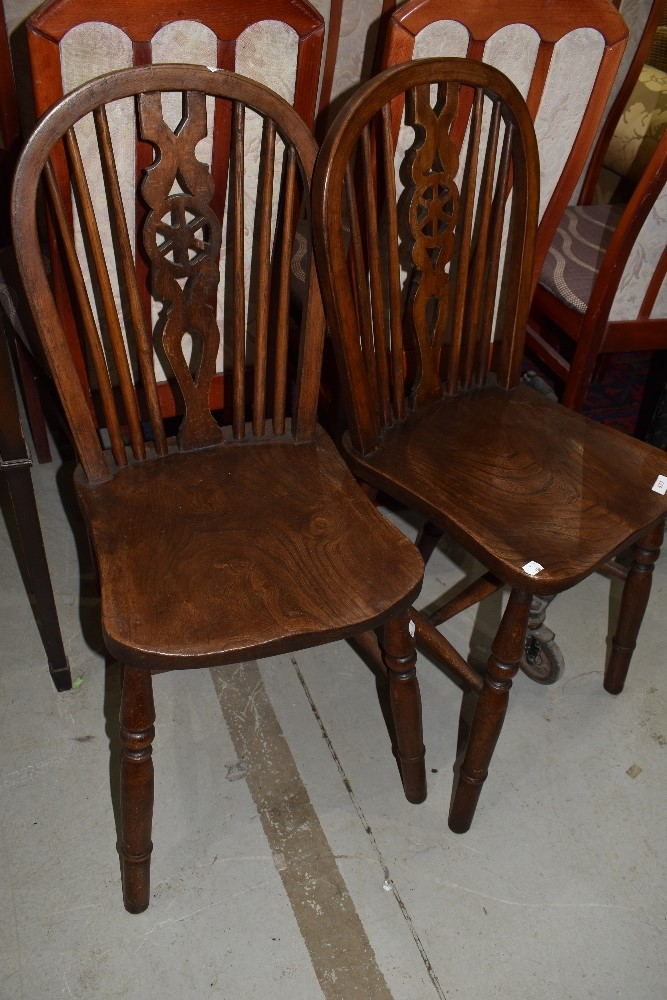 A pair of traditional oak wheel back solid seat kitchen chairs