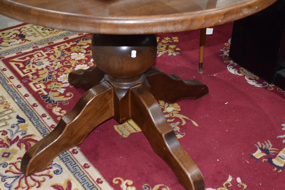 A modern oak circular dining table having bulbous column and chunky legs