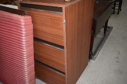 A laminate three drawer filing cabinet