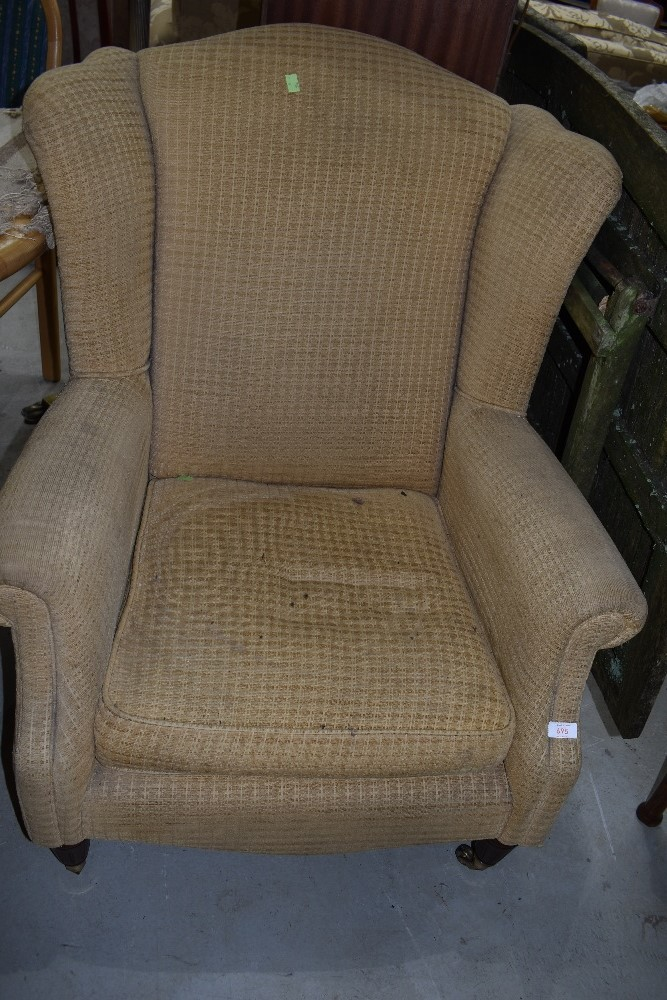 A reproduction wing back armchair