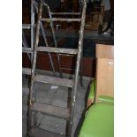 A set of fold away metal framed wooden step ladders